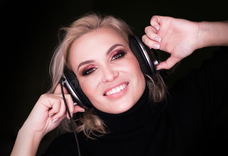 Musique de écoute de jeune fille blonde au-dessus de fond noir image libre de droits