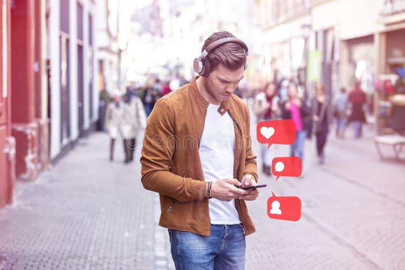 Musique de écoute de jeune homme adulte sur Smartphone et écouteur sur la rue à l'heure d'été image stock