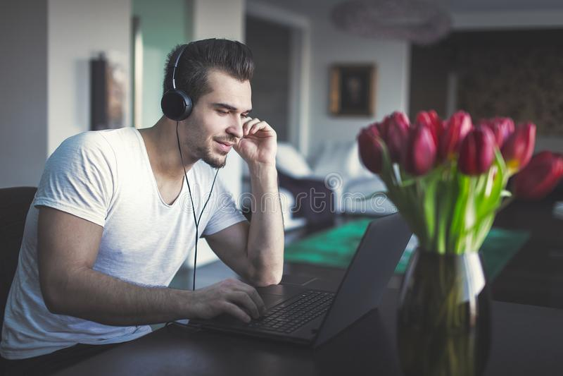 Musique de écoute de jeune homme par l'ordinateur portable à la maison photo libre de droits