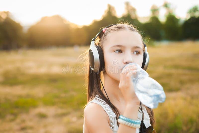 Musique de écoute de jolie fille et eau potable  photos libres de droits