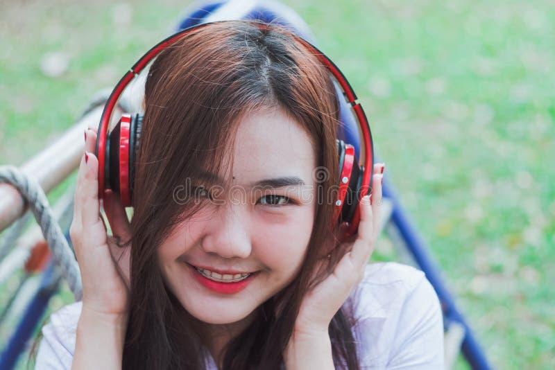 Musique de écoute de Madame de téléphone intelligent avec des écouteurs extérieurs photos stock