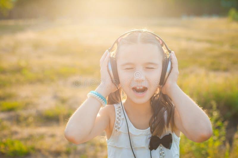Musique de écoute de petite fille avec des écouteurs image libre de droits