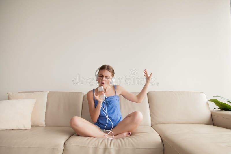 Musique de écoute de port d'écouteurs de jeune fille sur le smartphone à h photos stock