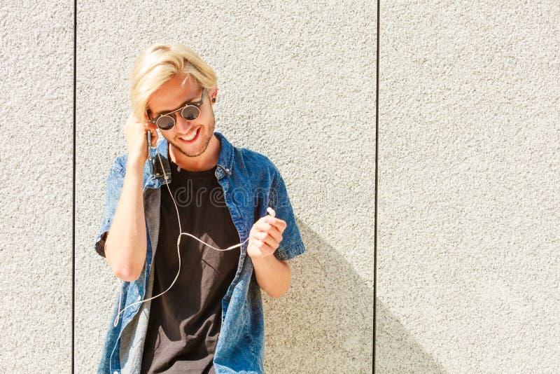 Musique de écoute de sourire d'homme de hippie par des écouteurs photographie stock