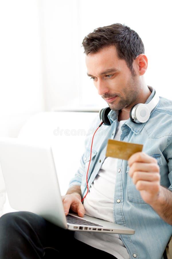 Musique de achat de jeune homme décontracté sur un ordinateur portable photos libres de droits