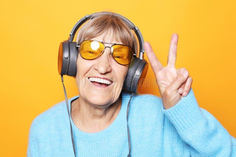 Musique de ?coute dr?le de vieille dame et de repr?sentation pouces  photographie stock