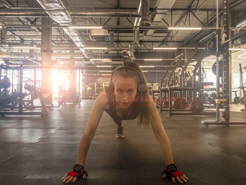 Musique de ?coute de femme de forme physique dans des ?couteurs sans fil Faire des exercices de séance d'entraînement dans le gym images libres de droits