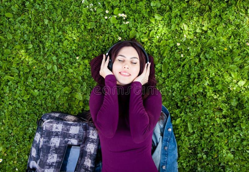 Musique de ?coute de jeune femme mignonne avec des ?couteurs photo stock