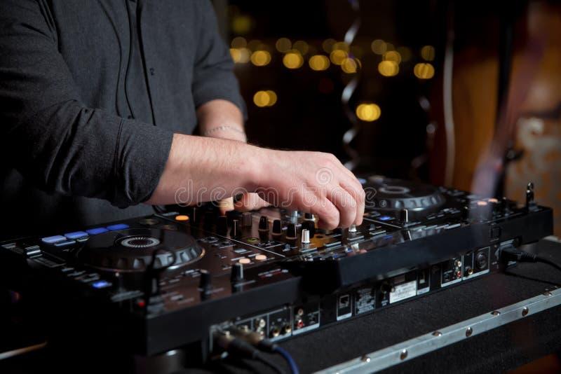 Musique de mélange de main sur le contrôleur du DJ avec les icônes sociales de concept de médias Le DJ jouant musique progressive photos stock