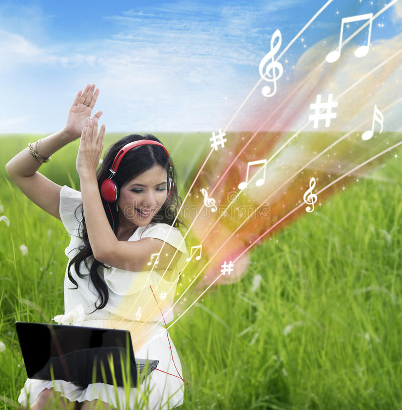 Musique Femelle Enthousiaste De Téléchargement De L Ordinateur Portable - Extérieur Images stock