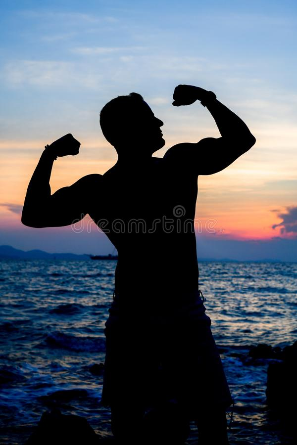 Muskel auf dem Strand Schattenbild auf Sonnenuntergang stockfotografie
