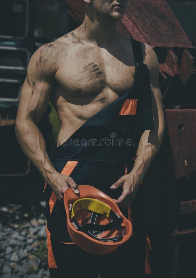 Muskelbegrepp Den färdiga kroppen i funktionsduglig likformig med biceps och tricepens tränga sig in Muskelbyggnad Muskelminne royaltyfri fotografi