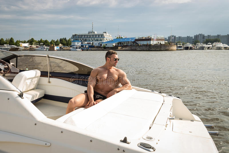 Muskelmann auf einem Boot stockfotos