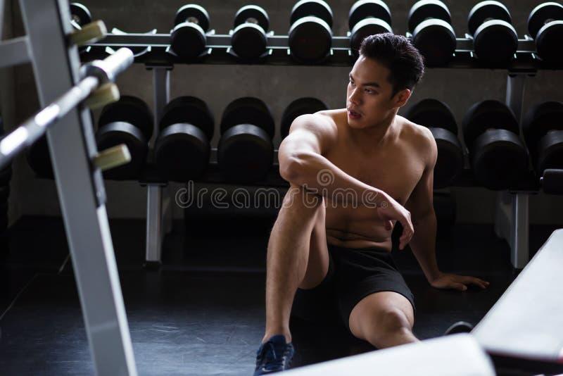 Muskelmannen vilar efter hantelövning arkivfoton