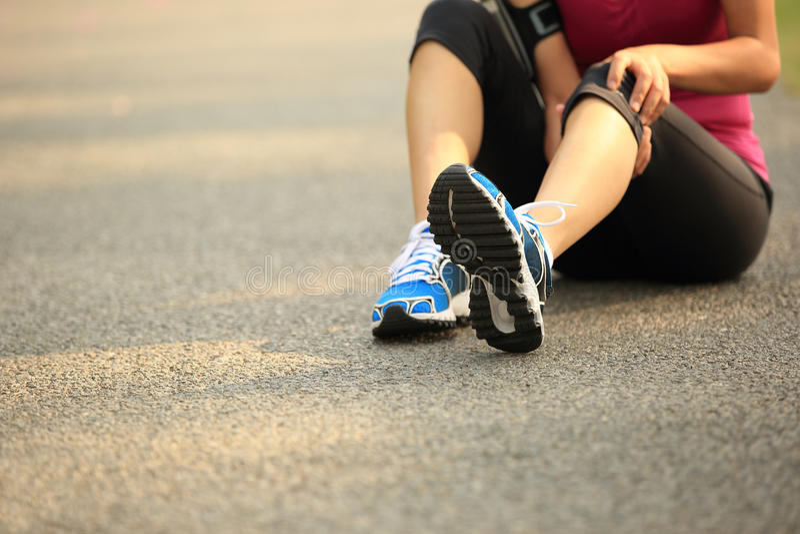 muskeln för closeupskadabenet smärtar för sportfläck för löpare running trycka på för lår arkivbild