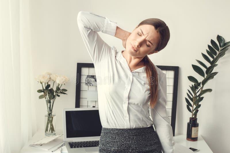 Muskeln för stil för begreppet för inrikesdepartementet för freelanceren för den unga kvinnan inomhus smärtar den formella arkivbild