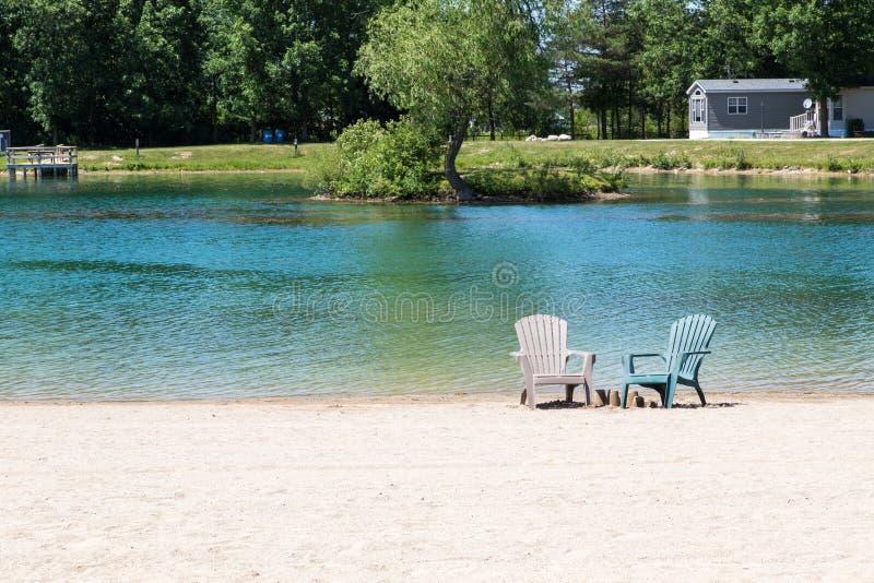 Muskoka stolar på stranden arkivbild