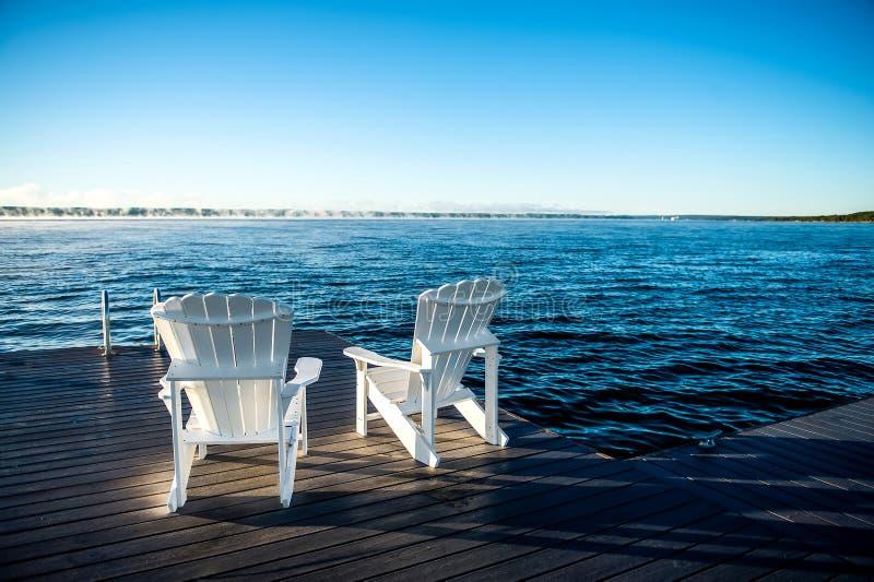 Muskokastoelen op een dok met zon het toenemen en mist royalty-vrije stock afbeeldingen