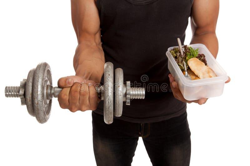 Muskulös asiatisk man med hanteln och ren mat i ask royaltyfri foto