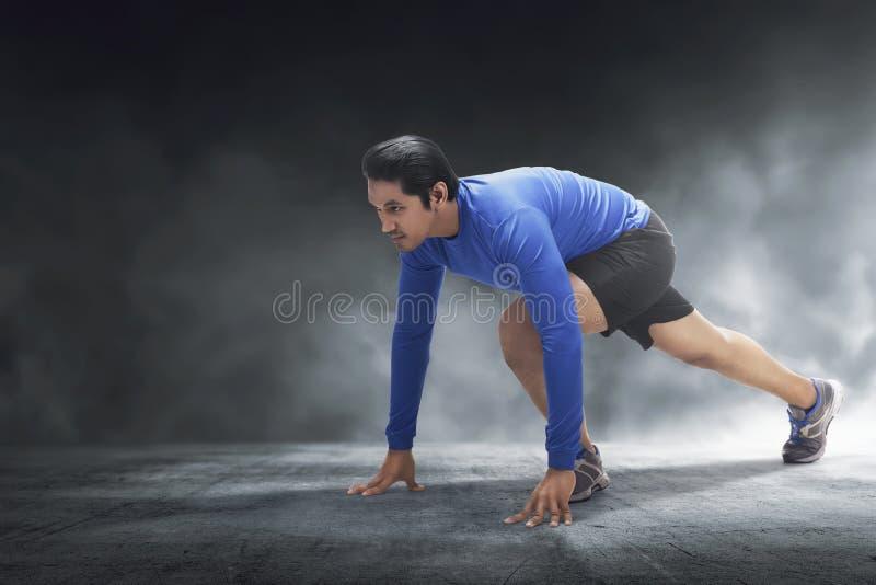 Muskulös asiatisk man som är klar för körning fotografering för bildbyråer