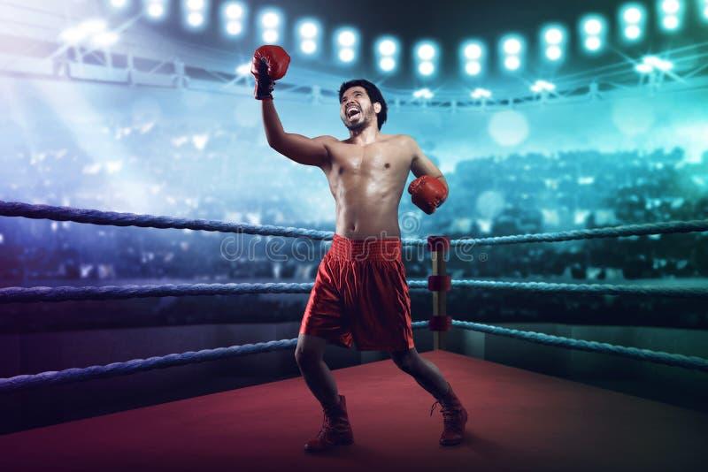 Muskulös asiatisk manlig boxare som kastar en uppercut royaltyfria bilder