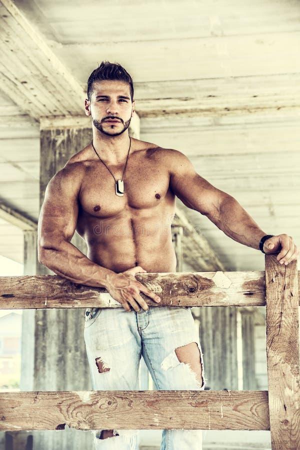 Muskulös byggnadsarbetare som är shirtless i byggnad fotografering för bildbyråer