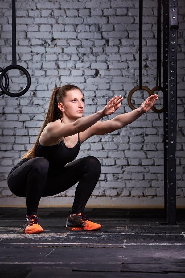 Muskulös härlig kvinna som gör squats i brutal inre Crossfit royaltyfri bild
