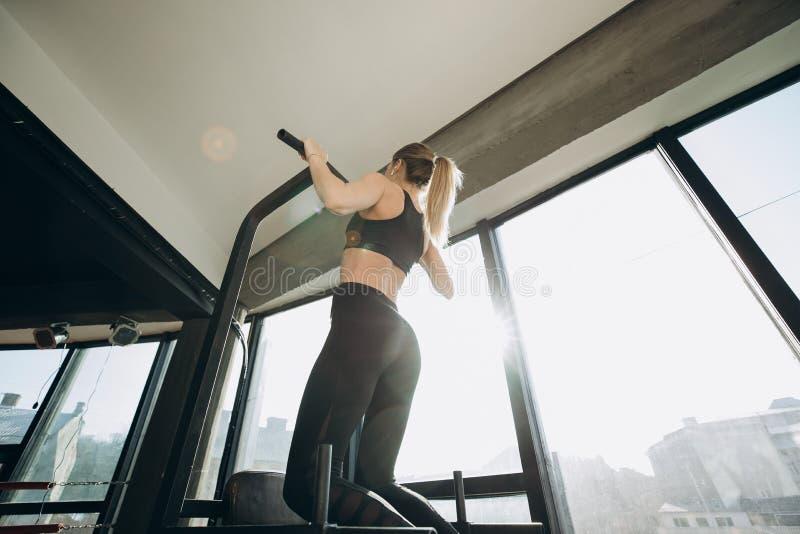 Muskulös idrotts- flicka, kroppsbyggare, i korta kortslutningar som dras på en sportsimulator royaltyfri fotografi