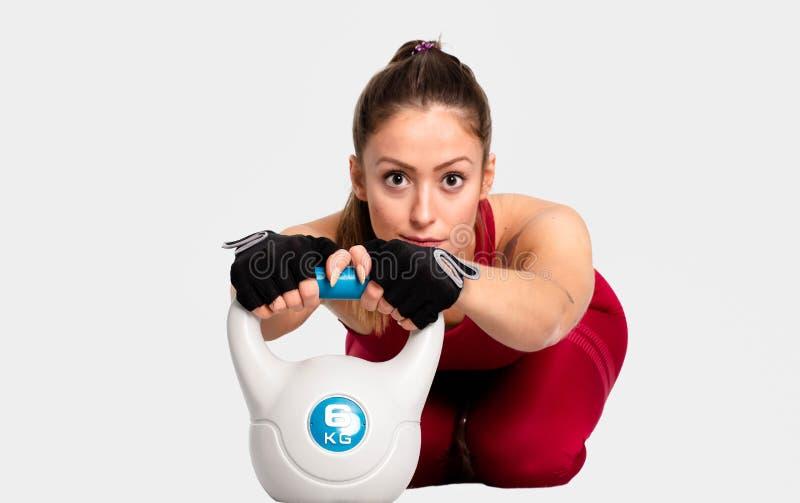 Muskulös idrottskvinna som värmer upp för en intensiv genomkörare med kokkärlklockan på säker vit bakgrund - bild royaltyfri fotografi