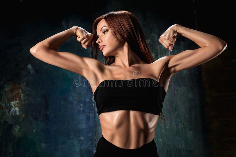 Muskulös idrottsman nen för ung kvinna på svart royaltyfri fotografi