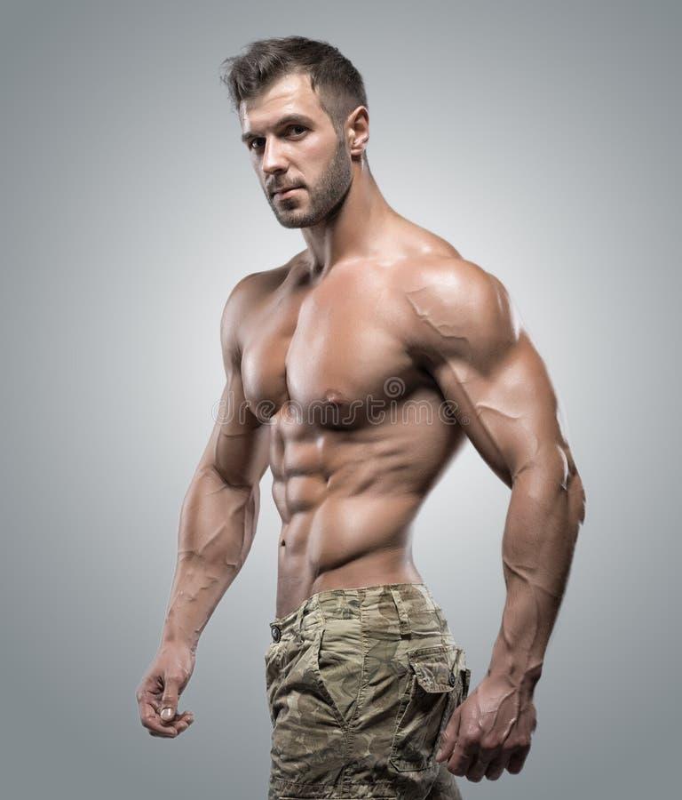 Muskulös idrottsman nenkroppsbyggareman på en grå bakgrund fotografering för bildbyråer