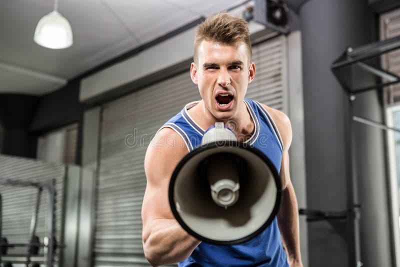 Muskulös instruktör som ropar på megafonen royaltyfri foto