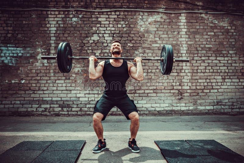 Muskulös konditionman som gör deadlift en skivstång över hans huvud i utomhus-, gataidrottshall Funktionell utbildning arkivfoton
