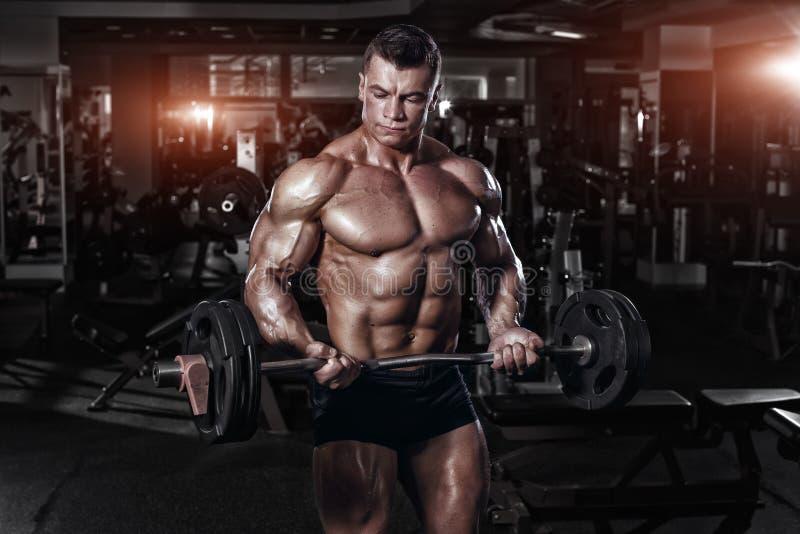 Muskulös kroppsbyggare för idrottsman nen i idrottshallutbildningen med stången royaltyfri fotografi