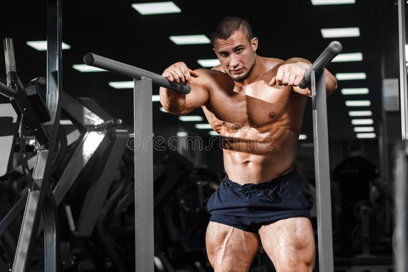 Muskulös kroppsbyggare som utarbetar i idrottshallen som gör övningar på paral arkivbild