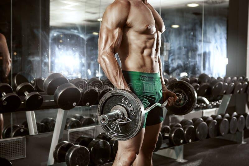 Muskulös kroppsbyggaregrabb som gör övningar med den stora hanteln royaltyfri fotografi