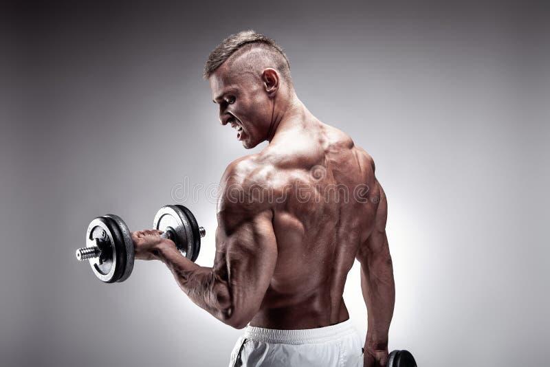 Muskulös kroppsbyggaregrabb som gör övningar med hanteln arkivfoto