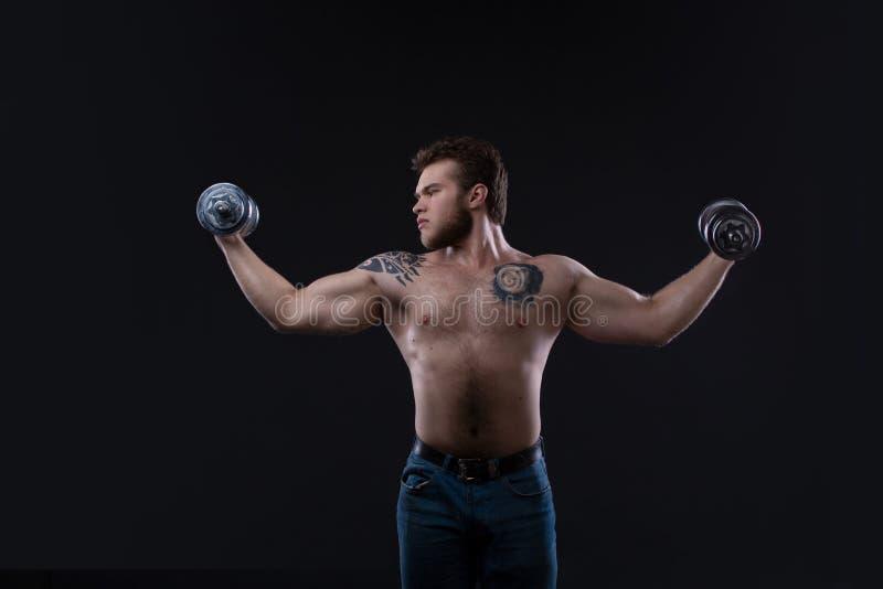Muskulös kroppsbyggaregrabb som gör övningar med hantlar över svart bakgrund royaltyfria foton