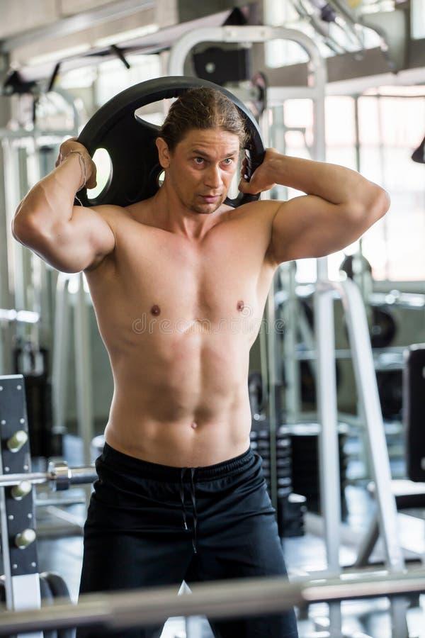 Muskulös kroppsbyggaregrabb som gör övningar med plattan för lyfta för vikt i idrottshall F?r konditionman f?r Shirtless sport un royaltyfri bild