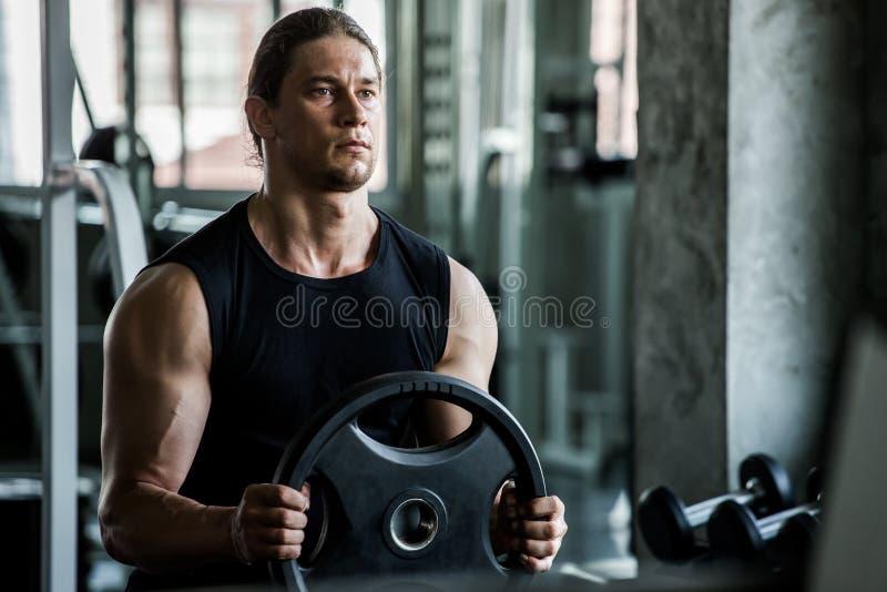 Muskulös kroppsbyggaregrabb som gör övningar med plattan för lyfta för vikt i idrottshall f?r konditionman f?r sport ung utbildni arkivfoto