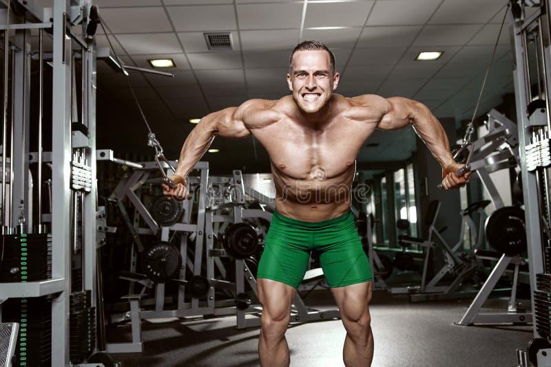 Muskulös kroppsbyggaregrabb som gör övningsgenomkörare i idrottshall royaltyfri foto