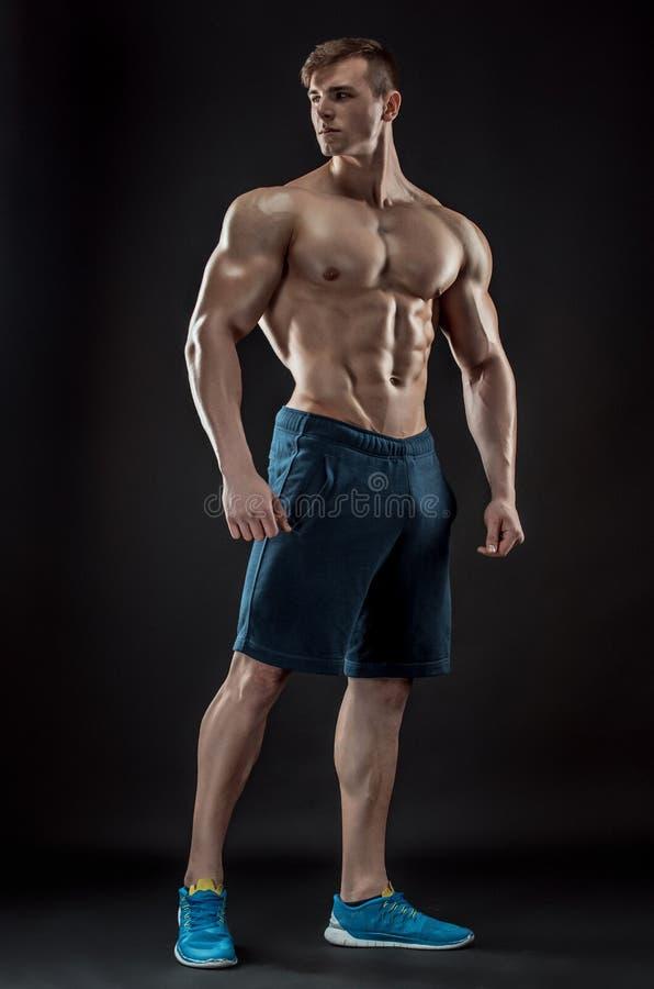 Muskulös kroppsbyggaregrabb som gör att posera över svart bakgrund arkivfoton