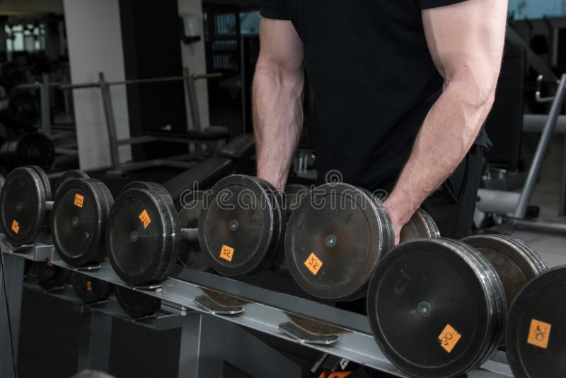 Muskulös kroppsbyggaregrabb som rymmer stora svarta järnhantlar i en idrottshall Mannen med den stora handen tränga sig in att ut royaltyfri bild
