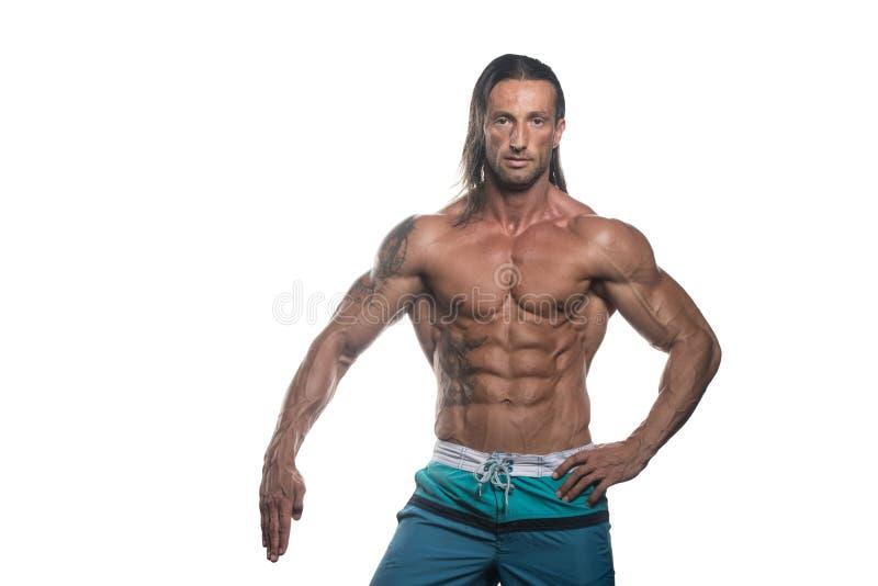 Muskulös kroppsbyggareman som poserar över vit bakgrund arkivfoton