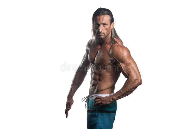 Muskulös kroppsbyggareman som poserar över vit bakgrund arkivbild