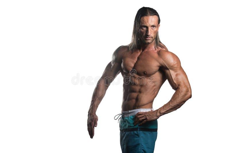 Muskulös kroppsbyggareman som poserar över vit bakgrund royaltyfri foto