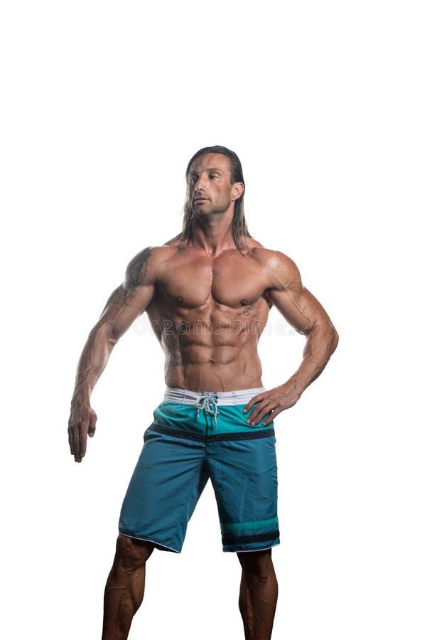 Muskulös kroppsbyggareman som poserar över vit bakgrund royaltyfri bild