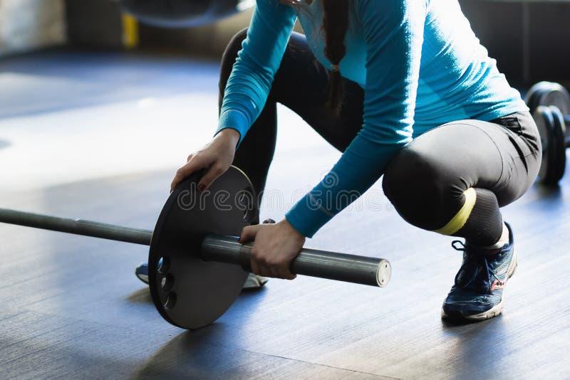 Muskulös kvinna i en idrottshall som gör deadlift arkivbild