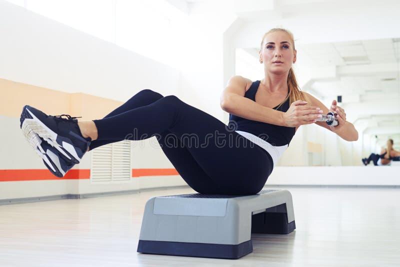 Muskulös kvinna med den slanka konditionkroppen som gör övningar med dumbb arkivbilder