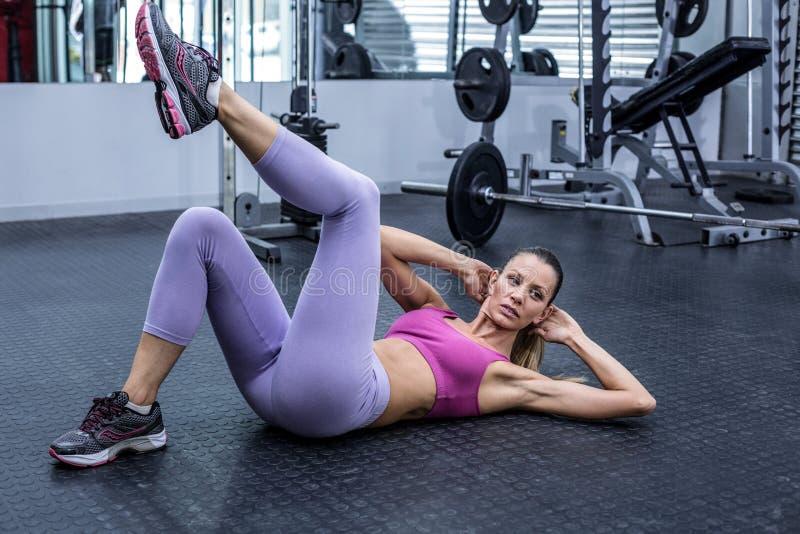 Muskulös kvinna som gör buk- knastrande royaltyfria bilder